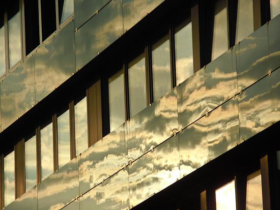 Sonne und Wolken spiegeln sich an eine Fassade