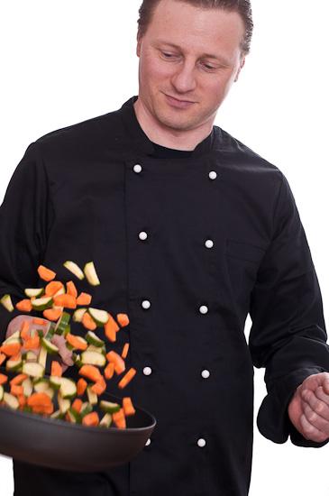 Koch wendet Gemüse in einer Pfanne