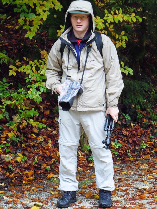 Fotograf mit Ausrüstung und Regenschutz