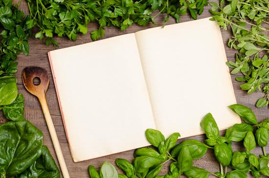 Leeres Kochbuch mit Kräutern